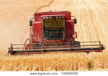 close front view of combine harvester in action