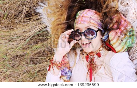 Dressed in boho chic style woman portrait lying on a hay and fur, close up, healthy and happy concept, autumn outdoor, with copy space for text