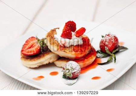 Pancake dessert with strawberries, cream and topping on white wooden table. Appetizing serving of sweet at restaurant