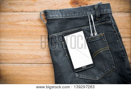 jeans with mobile phone and screwdriver tool in pocket on wooden board
