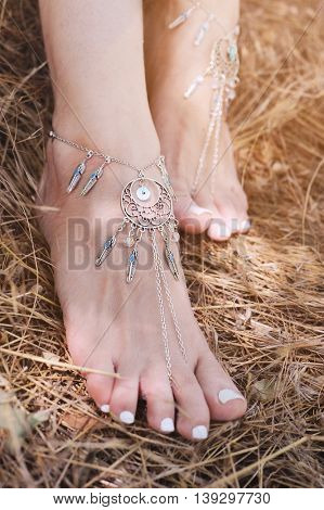 Handcrafted bracelets on a woman legs, close up, white pedicures, boho chic style, body care concept, sunny outdoor