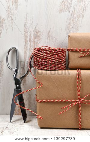 Closeup of plain brown paper wrapped Christmas presents with scissors and twine.