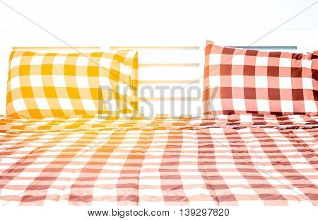 The Closeup Of Bed In Small Bedroom With Warm Light