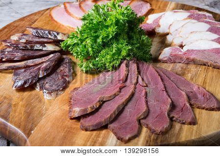 Different sorts of parma ham meat on wooden tray
