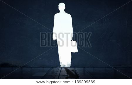 Silhouette of businessman in wall . Mixed media