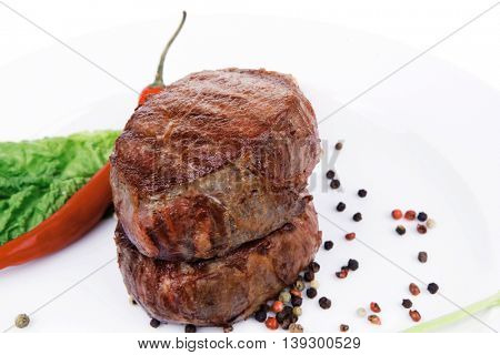 grilled beef fillet pieces on noodles , red hot chili pepper with tomato and green salad leaf on white plate isolated over white background