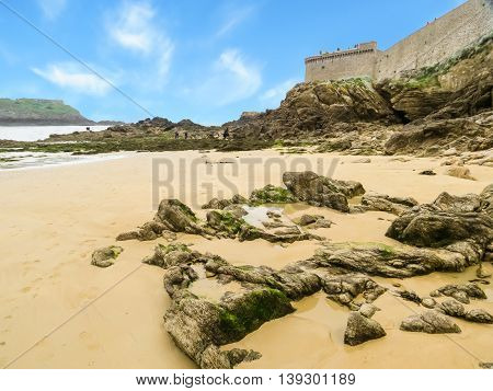 Medieval city walls and seacoast in low tide . Saint Malo, Brittany, France