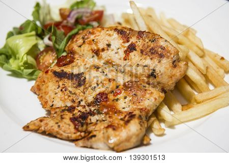 Grilled chicken breast served with fresh vegetable salad and chips