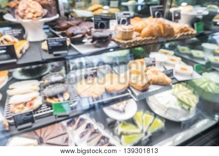 Abstract blur shop display window with variety of cakes