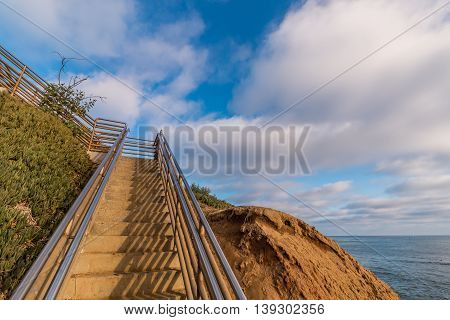 Staircase at Ladera Street going up a cliff with a cloudy sky background at Sunset Cliffs in San Diego, California.