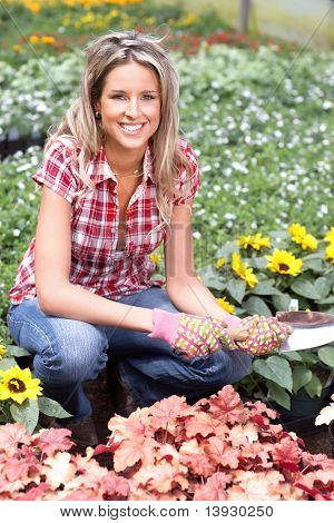 Young smiling woman florist working in the garden