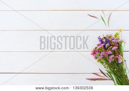 Bunch of field flowers on white wooden background, copyspace for text or advertising. Rustic floral composition