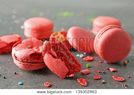 Red broken tasty macaroons on gray background