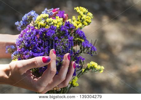 Young girl is holding a bouquet of wildflowers.
