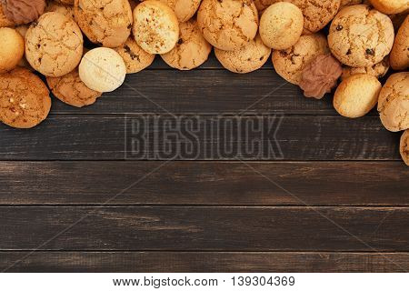 Cookies and sweet biscuits at brown wood, background with copy space. Oatmeal and chocolate drops cookies border, dessert for tea.