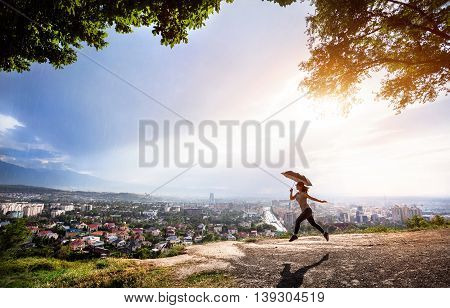 Woman With Umbrella Jumping Over Cityscape At Sunset