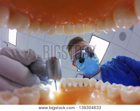 Dentist in loops drilling teeth during dental appointment