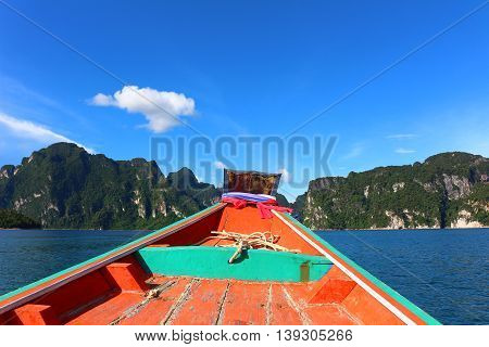 Red painted boat in the water with mountains and clear blue sky
