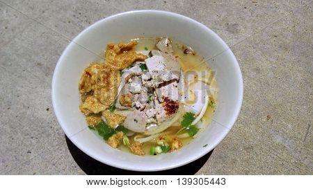 Wide wet rice noodles soup and fried dumplings