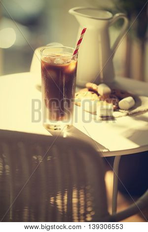 Iced coffee with straw on white table in cafe