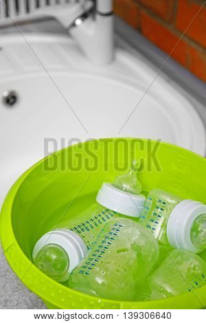 Sterilizing baby bottles in plastic green basin
