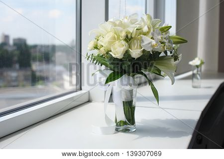 Beautiful wedding bouquet in a glass vase. Flowers on white windowsill. Boutonniere in a small vase. The window in the background.