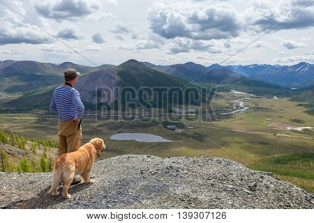 Man and his faithful friend the dog admire the mountain scenery in the campaign