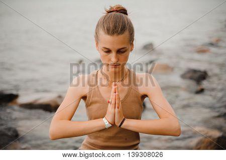 beautiful woman performing namaste with closed eyes gesture on beach