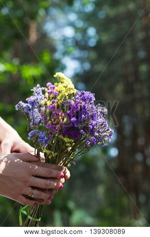 Loving couple are holding the bouquet of wildflowers.