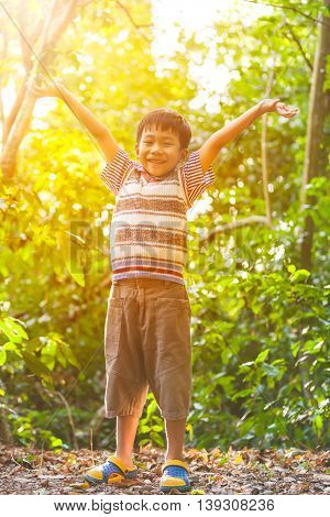 Happy asian boy smiling at forest travel on vacation. Cute child relaxing outdoors in the day time with bright sunlight.