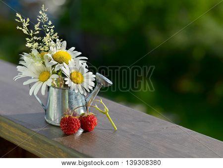 Summer still life with ripe berries, vintage watering can and flowers. Seasonal background with daisy and strawberry, rural countryside or retro garden concept