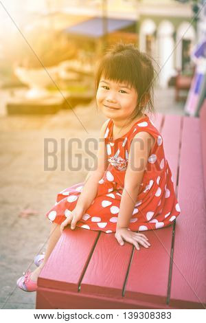Happy asian girl smiling and looking at camera. Child relaxing outdoors in the day time with bright sunlight travel on vacation.