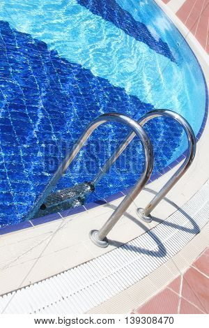Part of the swimming pool with metal ladder