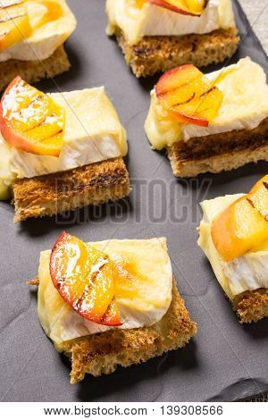 canapes Appetizer with grilled brie and nectarine plated on a slate dish