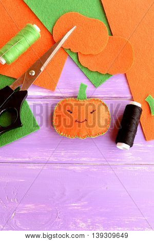Orange felt pumpkin toy, scissors, thread, felt sheets, pumpkin patterns on the wooden background with blank space for text. Halloween activities for children.
