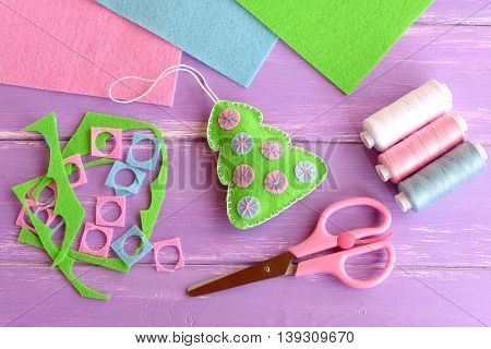 Green Christmas tree with balls, scissors, felt scraps, thread set, felt sheets on lilac wooden background. Christmas DIY background. Children winter crafts project. Sewing concept