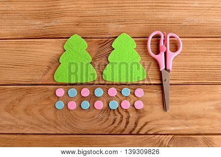 Felt Christmas tree patterns, pink and blue balls, scissors on wooden background with empty space for text. Felt Christmas tree DIY. Objects cut from felt. Top view. Tutorial for kids