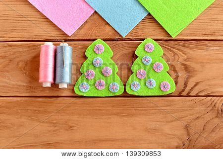 Green felt Christmas tree ornament with pink and blue balls on a wooden background. Christmas tree felt embroidery. Home embellishment. Sewing tutorial for kids. Top view. Closeup
