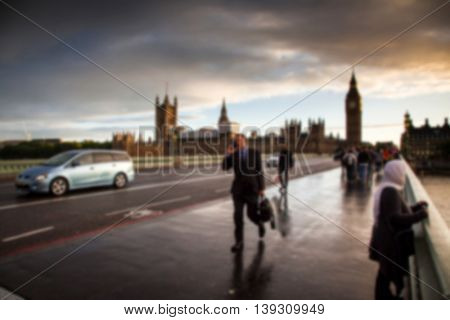 Blurred background of Big Ben at sunset on a rainy day, people with umbrellas, Westminster, London, UK
