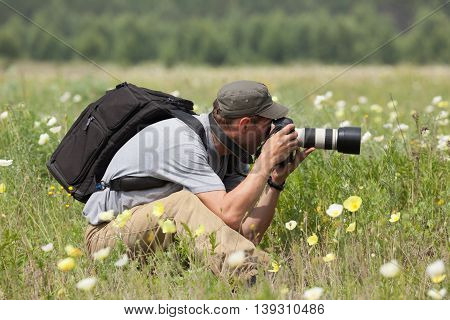 Photographer is taking a picture on green meadow in summer.