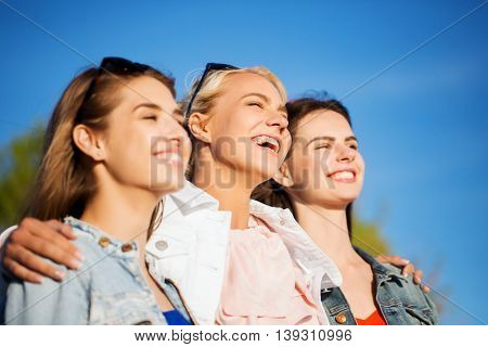 summer vacation, holidays, friendship and people concept - group of happy smiling young women or teenage girls hugging outdoors