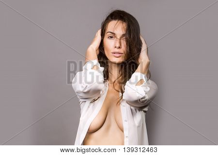 young sexy woman with pretty face and long brunette curly hair in white shirt has slim body in studio on grey background
