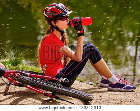 Bicycling girl. Girl wearing bicycling helmet rides bicycle. Girl bicycling drinking of bottle water. Bicycling is good for health concept.