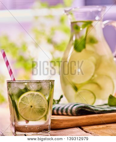 Country drink. On wooden boards is glass jug and glass with transparent drink and lime . A drink number hundred and ninety four with ice cubes . Country life. Light background.