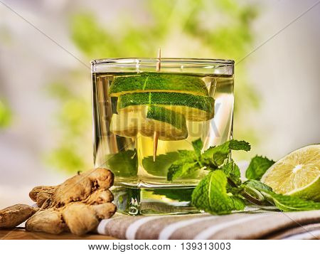 Healthy detox drink with ginger . On wooden boards short glass with green tea and mint. A mint ginger drink number one hundred eighty seven with half lime and napkin. Country life. Light background.