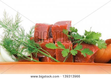 raw fresh beef meat slices in a ceramic dish with garlic and peppers isolated over white backkground