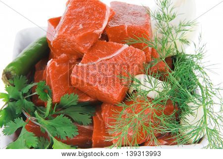 slices of raw fresh beef meat fillet in a white bowls with dill and green peppers isolated over white background