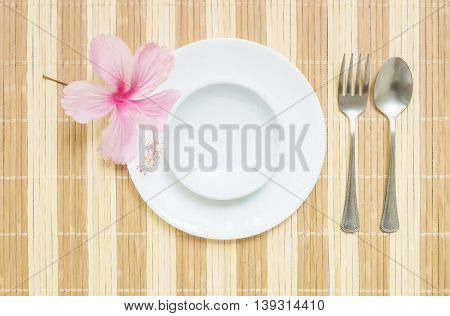Closeup white ceramic cup for soup on white dish with stainless fork and spoon on blurred wood mat textured background