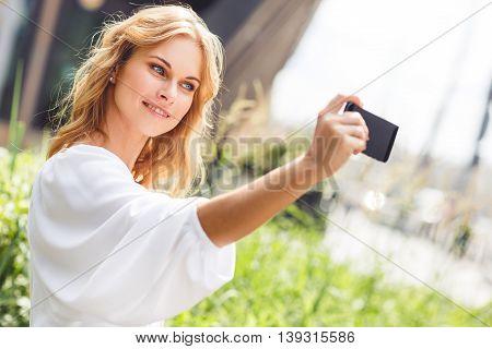 Portrait of beautiful girl on street in summer making self portrait on phone