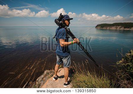 man photographer holding his camera. lake background